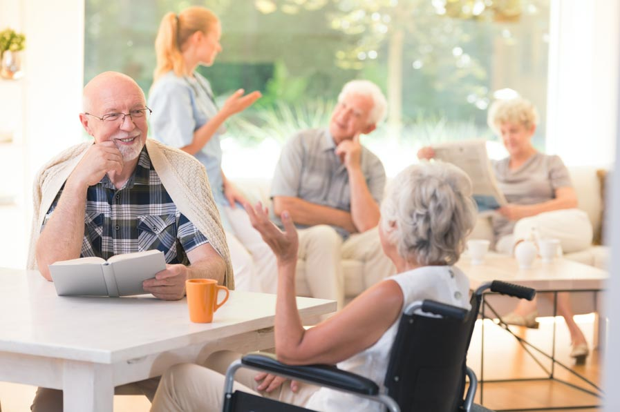 Elderly man and woman speaking at an assisted living community