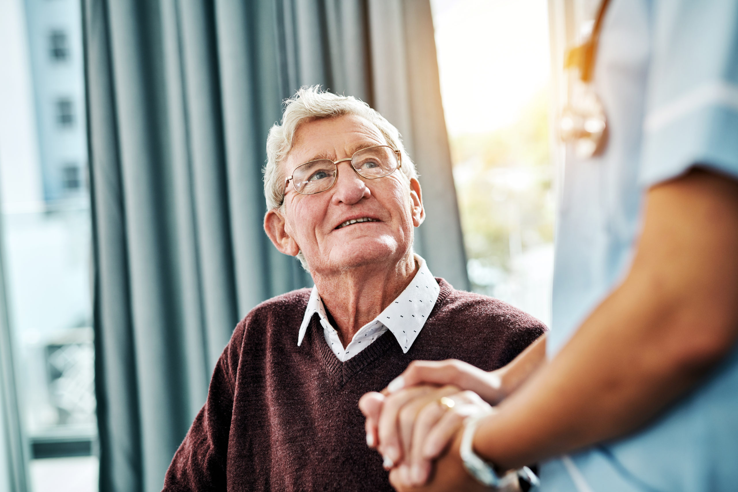 Cropped shot of a nurse holding hands with a senior patient